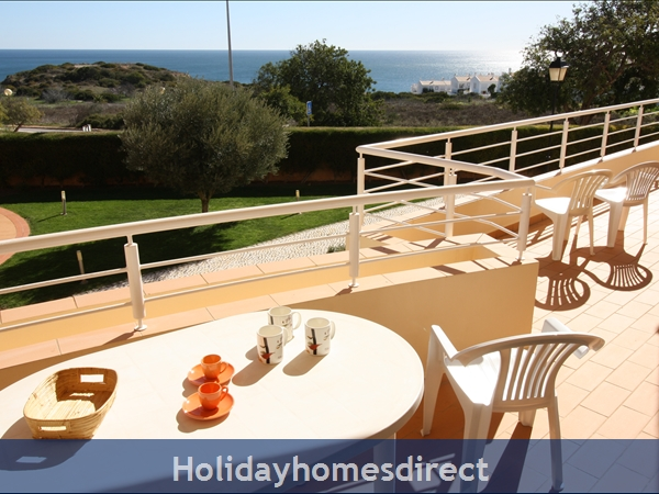 Sunny veranda has pool and sea views